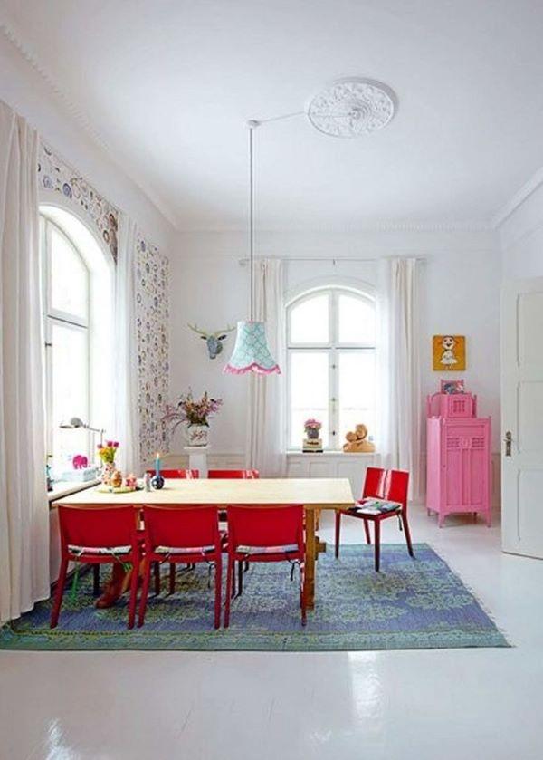 Sala de estar grande decorada com cadeira vermelha e tapete azul