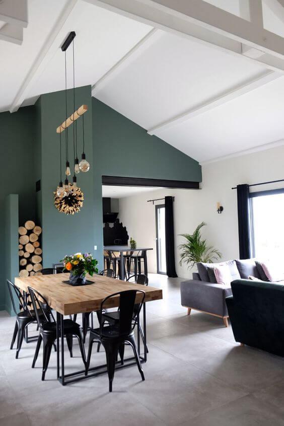 Sala de jantar com porcelanato cimento queimado e parede verde