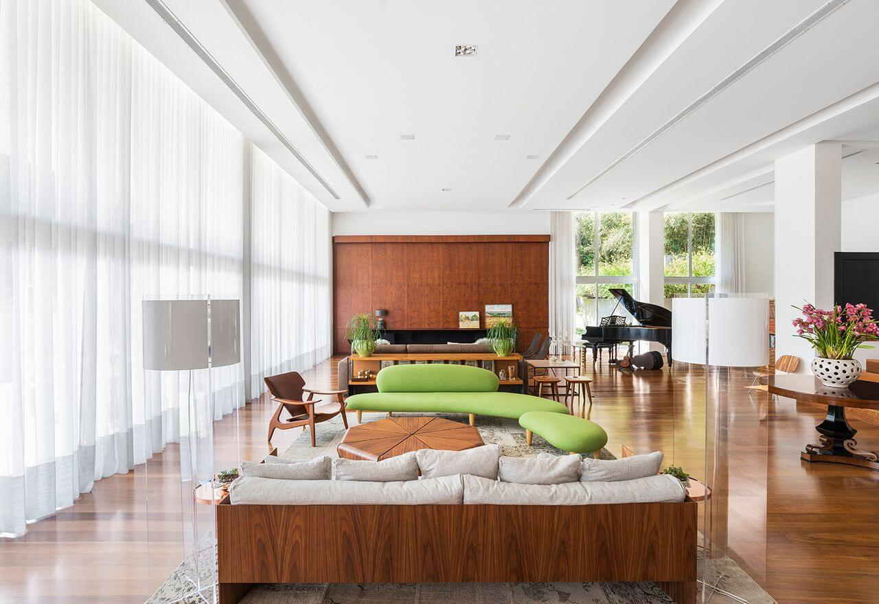 Sala grande decorada com criatividade e sofá verde e móveis de madeira