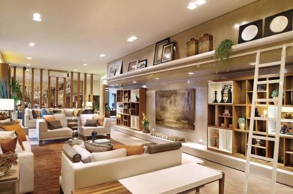 Sala grande decorada com estante planejada e prateleira decorada com quadros e enfeites variados