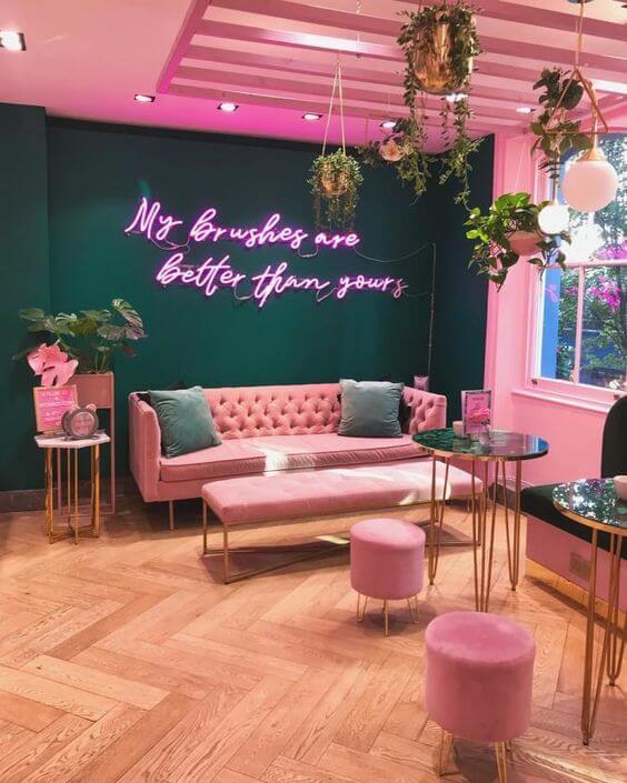 Sala grande decorada com estilo moderno com luz neon rosa na parede verde esmeralda