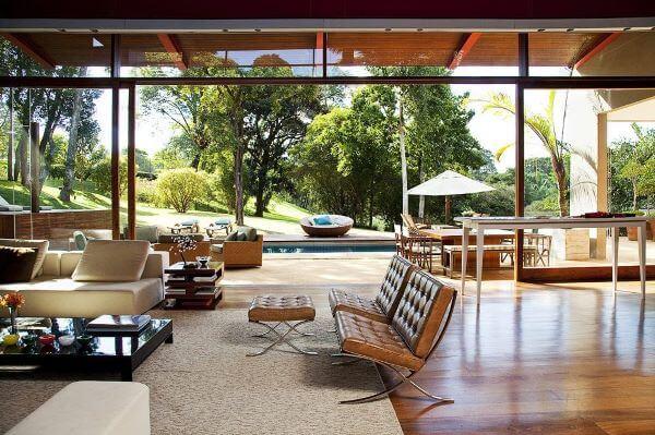 Sala grande decorada com móveis de couro e abertura para piscina