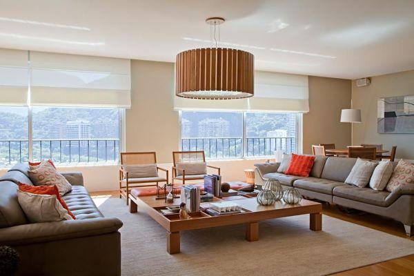 Sala grande decorada com móveis neutros e de madeira