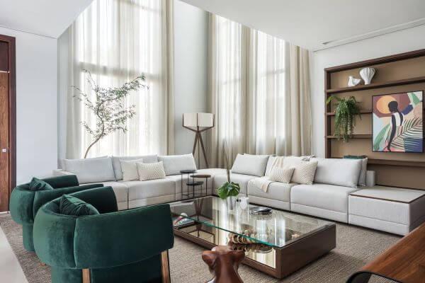 Sala grande decorada com poltronas verdes e sofás bege