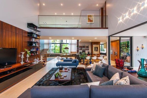 Sala grande decorada com sofá azul e tapete estampado