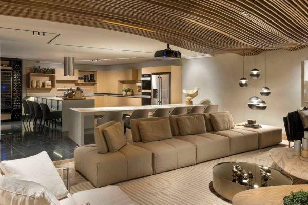 Sala grande decorada com sofá bege e cozinha americana