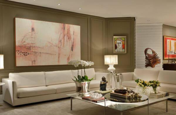 Sala grande decorada com sofá bege e parede marrom claro