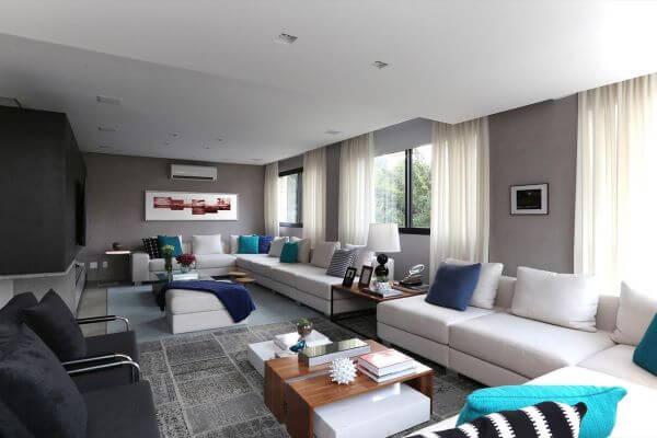 Sala grande decorada com sofá branco e almofadas em tons de azul