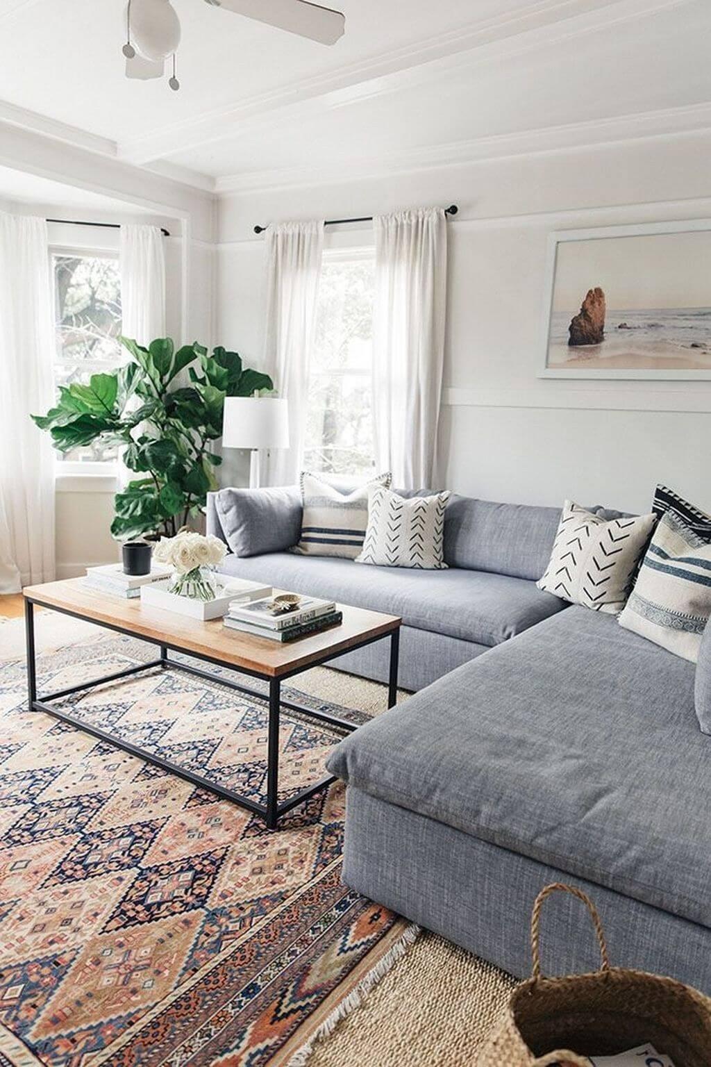 Sala grande decorada com sofá cinza e tapete estampado