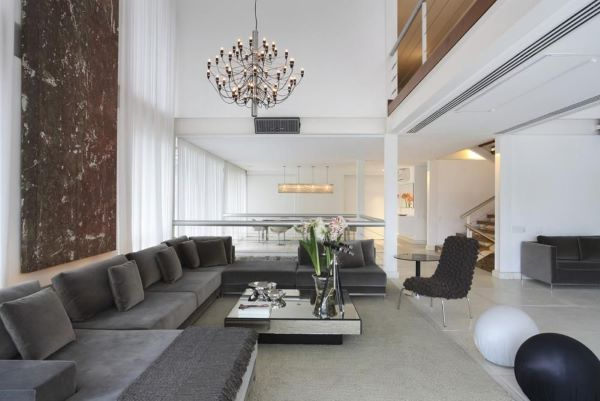Sala grande decorada com sofá grande cinza e decoração moderna
