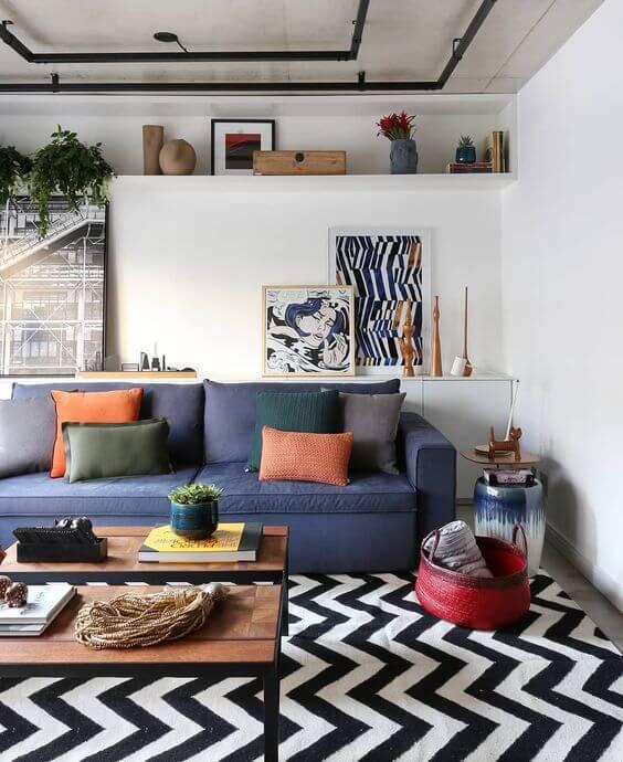 Sala grande decorada com tapete chevron e sofá azul