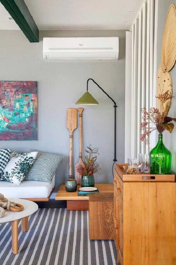 Sala grande decorada com tapete listrado e luminária de parede moderna