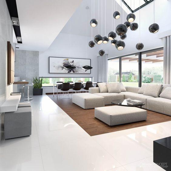 Sala grande decorada com tons claros e luxuosos com destalhe no lustre preto