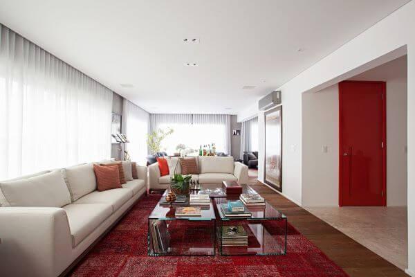 Sala grande decorada com tons de bege e vermelho com mesa de centro de vidro