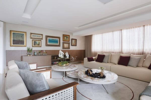 Sala grande decorada em tons claros e suaves e quadros classicos na parede