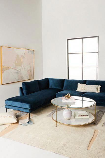 Sala minimalista e branca com sofá azul marinho de canto