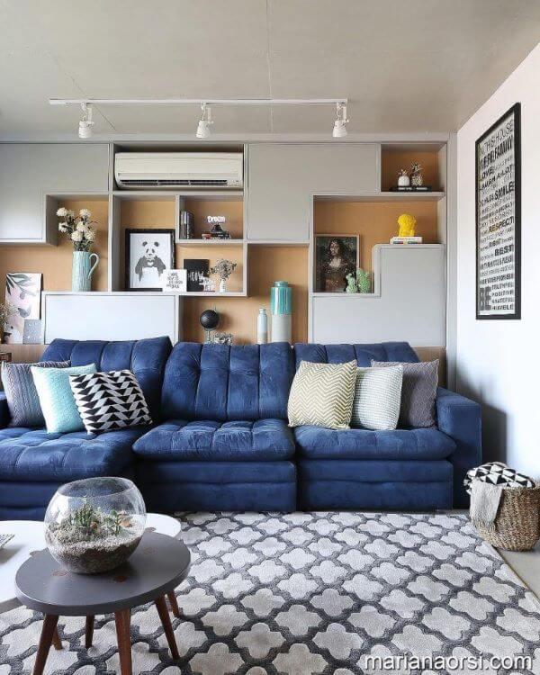 Sofá azul marinho na sala grande decorada e moderna com tapete estampado cinza