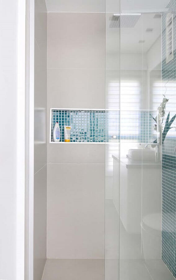 banheiro com pastilha de vidro azul no nicho e parede de box Foto Pinosy