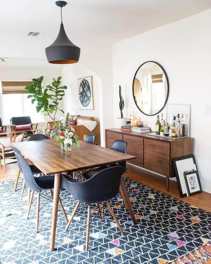 buffet de madeira para sala de jantar decorada com espelho redondo e tapete preto com detalhes coloridos Foto LIV Decora