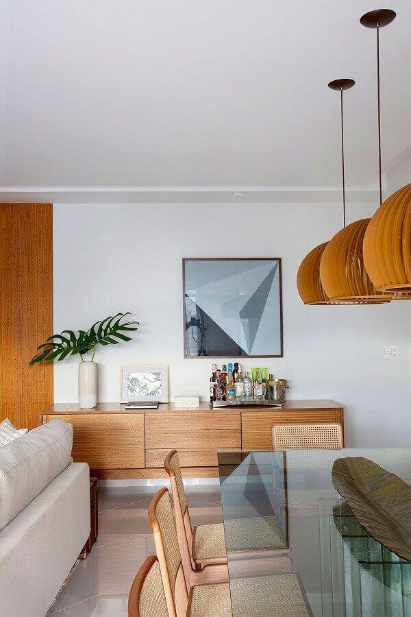 buffet de madeira para sala de jantar decorada com mesa de vidro e luminária redonda de madeira  Foto Casa de Valentina