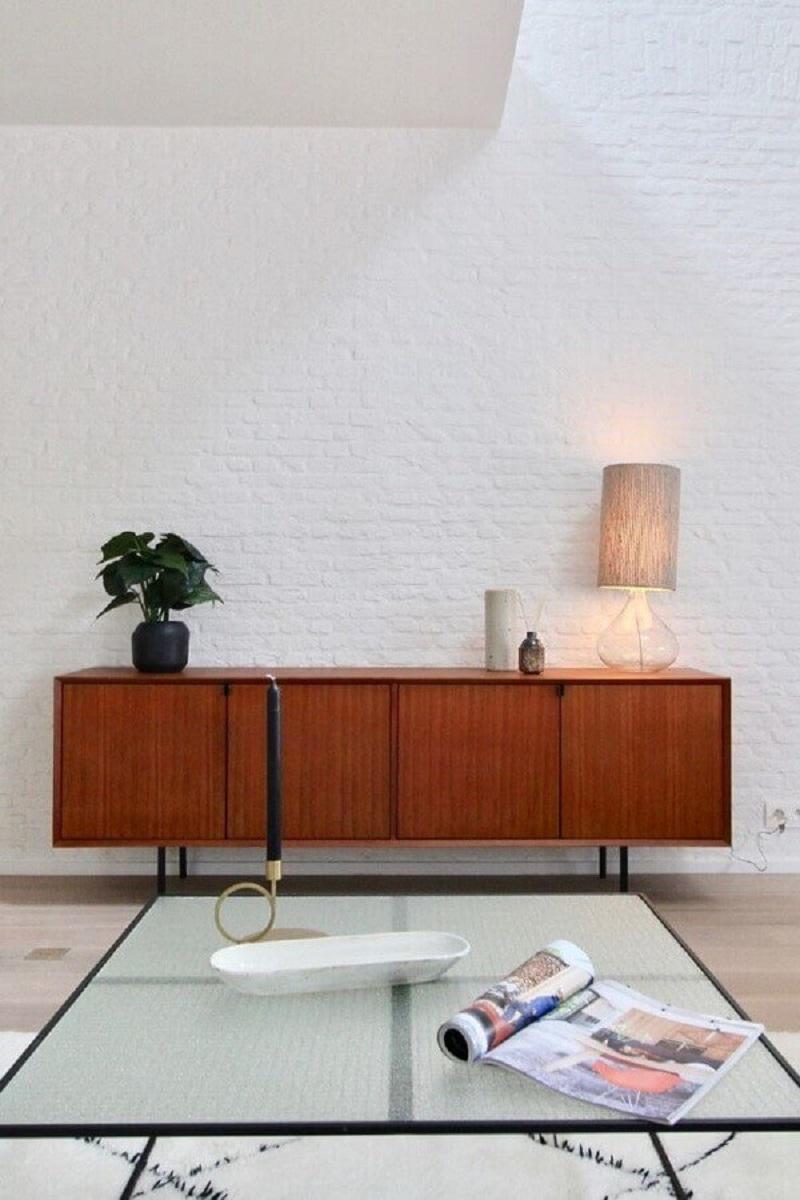 buffet de madeira para sala minimalista decorada com parede de tijolinho branco  Foto Apartment Therapy