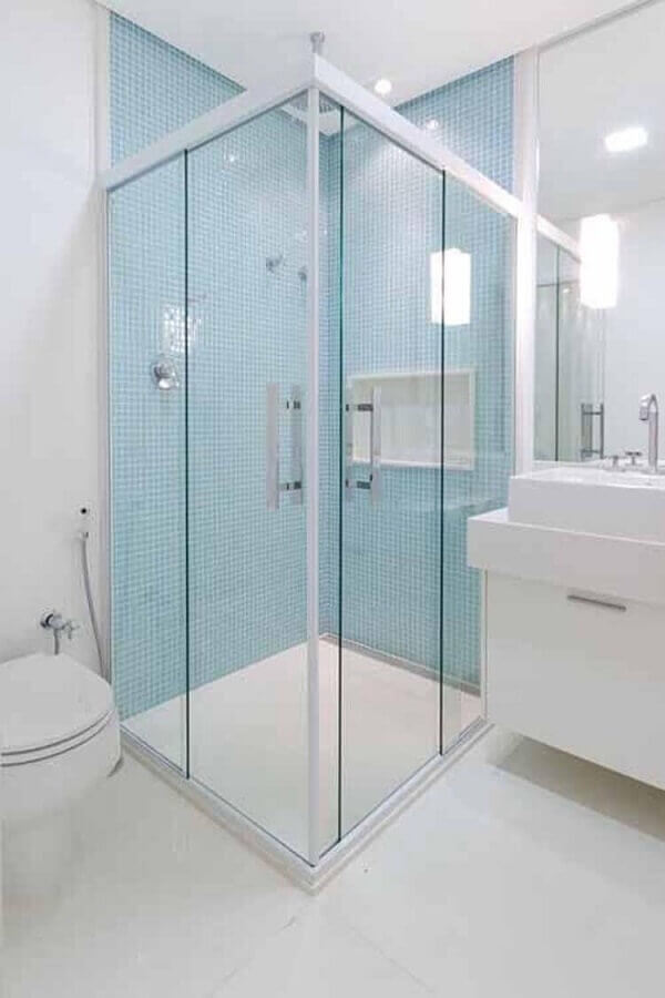 decoração banheiro branco com pastilhas de vidro azul dentro do box Foto Camila Tannous