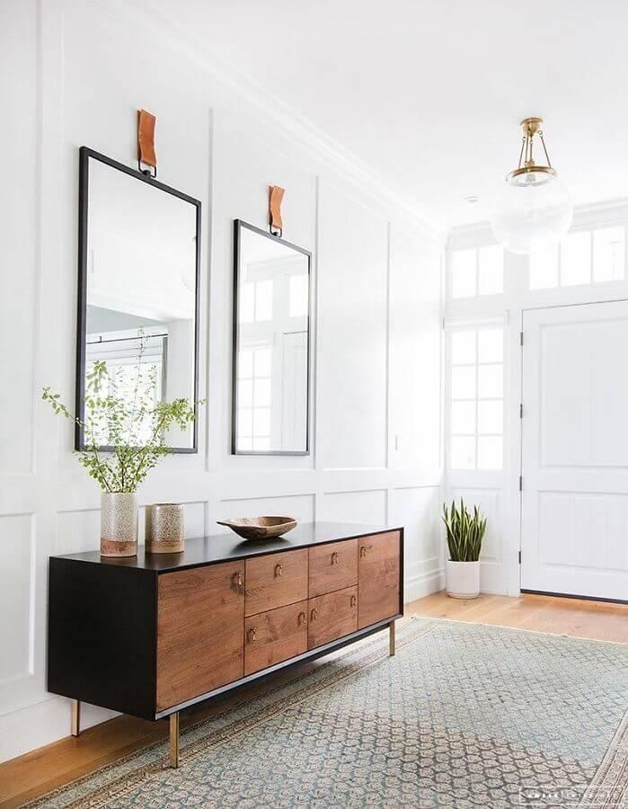 hall branco decorado com espelho grande e buffet de madeira Foto Apartment Therapy