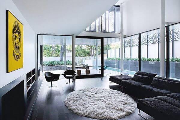 piso vinilico preto para decoração de sala grande com tapete redondo felpudo