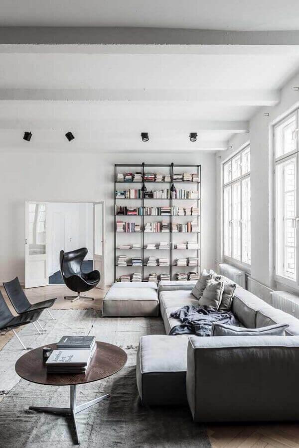 Poltrona giratória preta para sala grande decorada com sofá modular e estante de livros