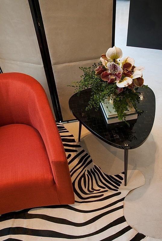 poltrona vermelha - mesa de canto preta e tapete de zebra