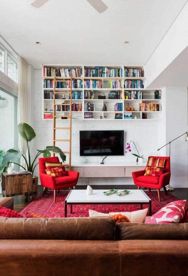 poltrona vermelha para sala decorada com sofá de couro e nichos para livros Foto Jeito de Casa