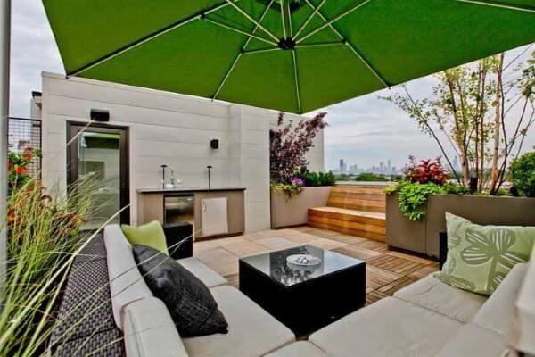 Área da piscina com deck de madeira e ombrelone