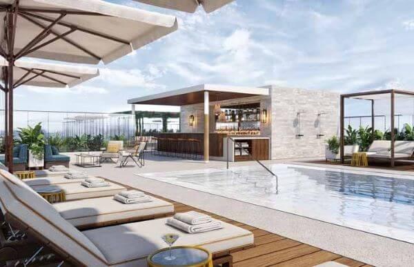 Área da piscina com guarda sol espreguiçadeiras e deck de madeira