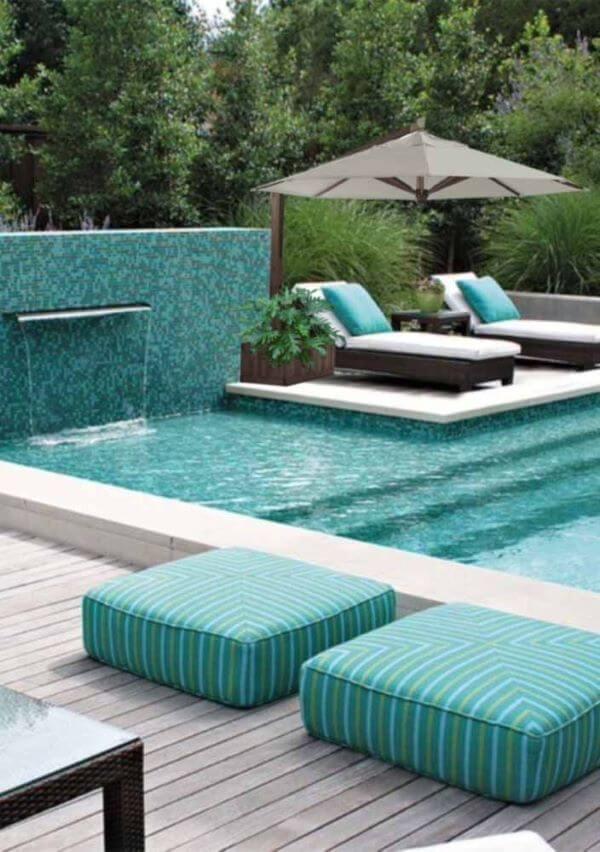 Área de piscina no quintal com guarda sol perto das espreguiçadeiras