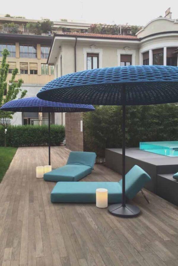 Área externa com guarda sol para piscina grande e azul