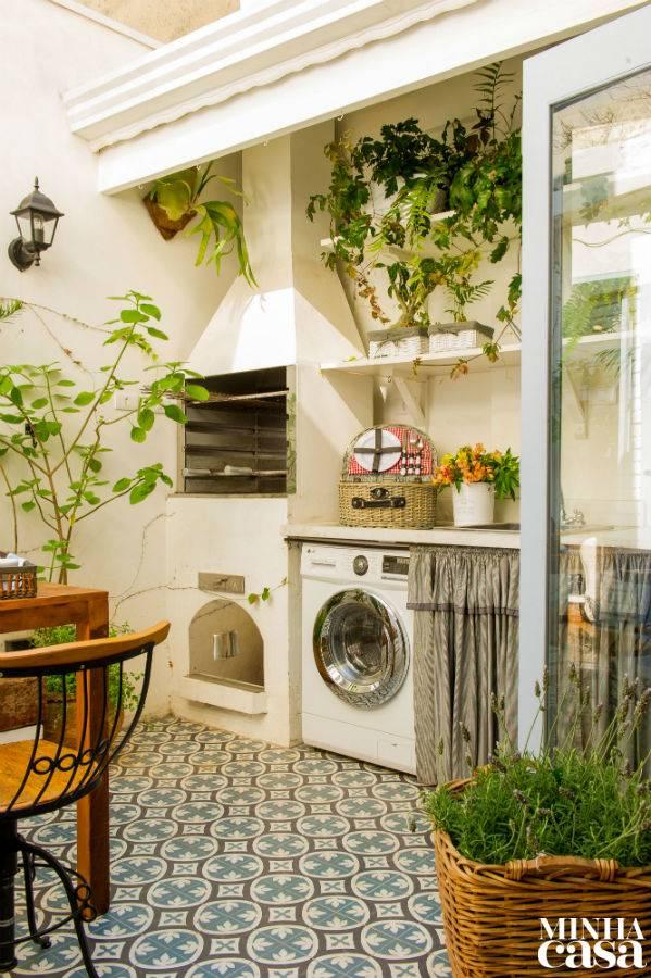 Área gourmet com lavanderia ao lado da churrasqueira com chaminé branca e alta