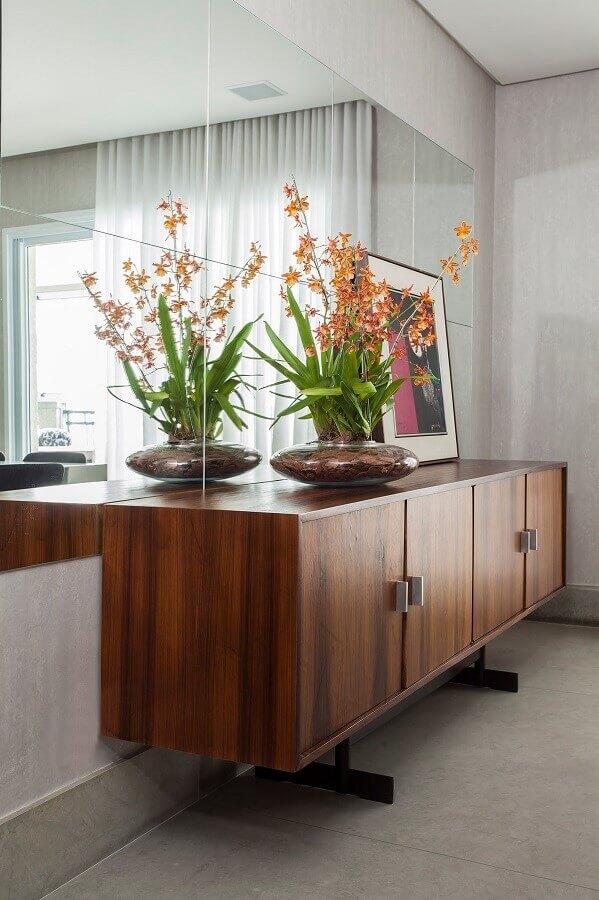 sala de jantar decorada com parede espelhada e buffet de madeira Foto A Gazeta