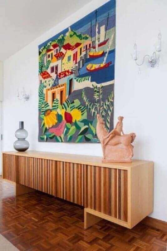 sala de jantar decorada com quadro grande colorido e buffet de madeira moderno Foto Jeito de Casa