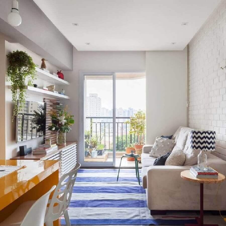 Ideia de cores para sala de estar pequena decorada com tapete listrado azul e branco Foto Tria Arquitetura