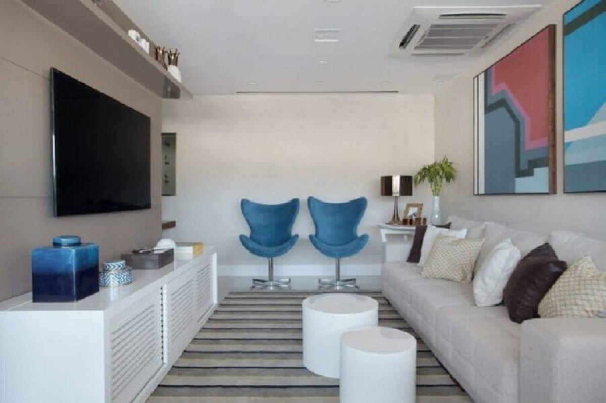 Cores para pintar sala pequena decorada com tapete listrado e quadros coloridos Foto Mariana Martini