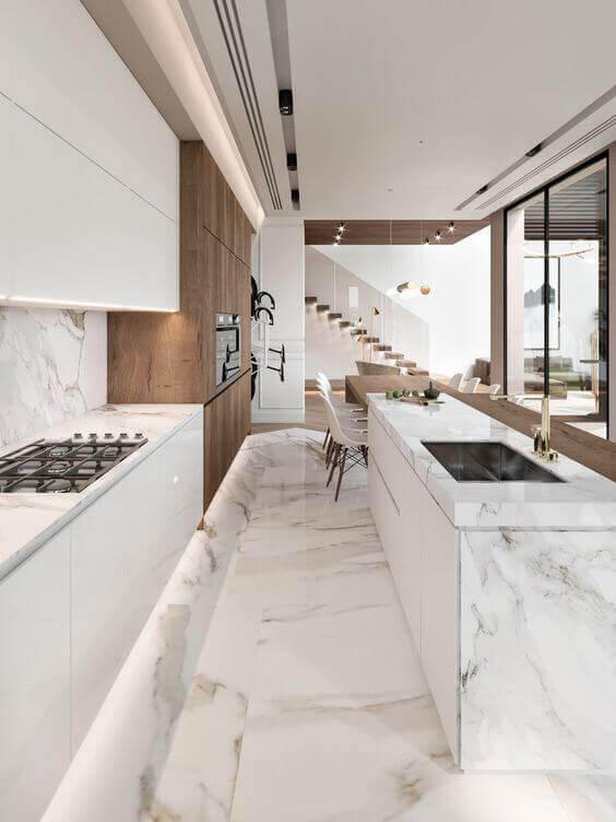 Cozinha branca revestida de porcelanato marmorizado