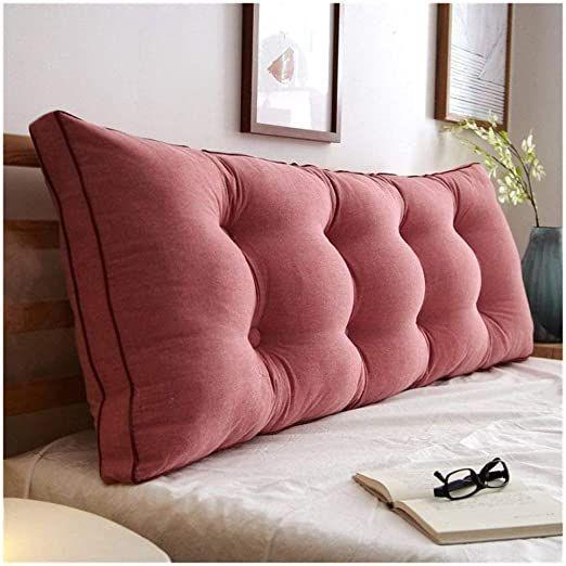 Almofada rosa para apoiar na cabeceira de madeira