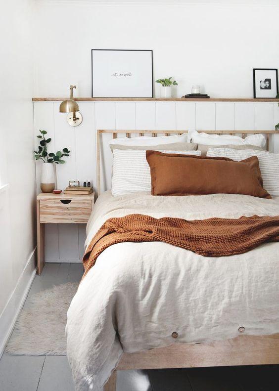 Quarto com cabeceira feita de almofada e estrutura de madeira