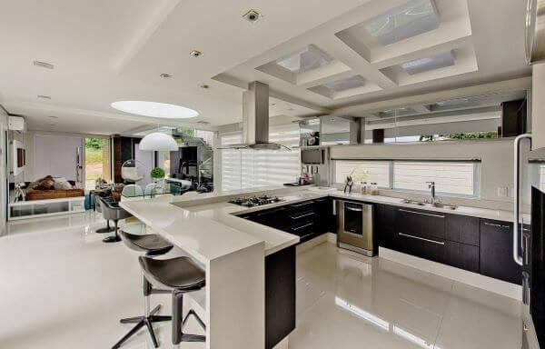 Cozinha americana com armário de vidro e bancada em u de granito