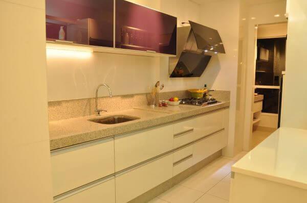 Cozinha planejada com armário de vidro roxo e bancada de granito bege