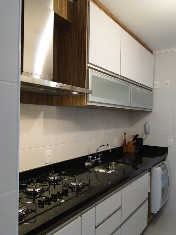 Cozinha moderna com bancada de granito e armário aéreo de vidro