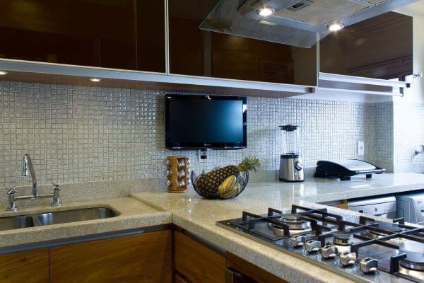 Revestimento para cozinha com pastilhas na cor prata e armário de vidro preto
