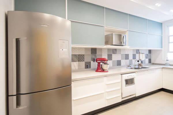 Cozinha com bancada de quartzo branco e armários azul claro
