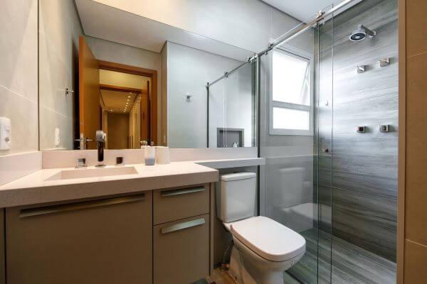 Banheiro com bancada de quartzo branco e pia esculpida