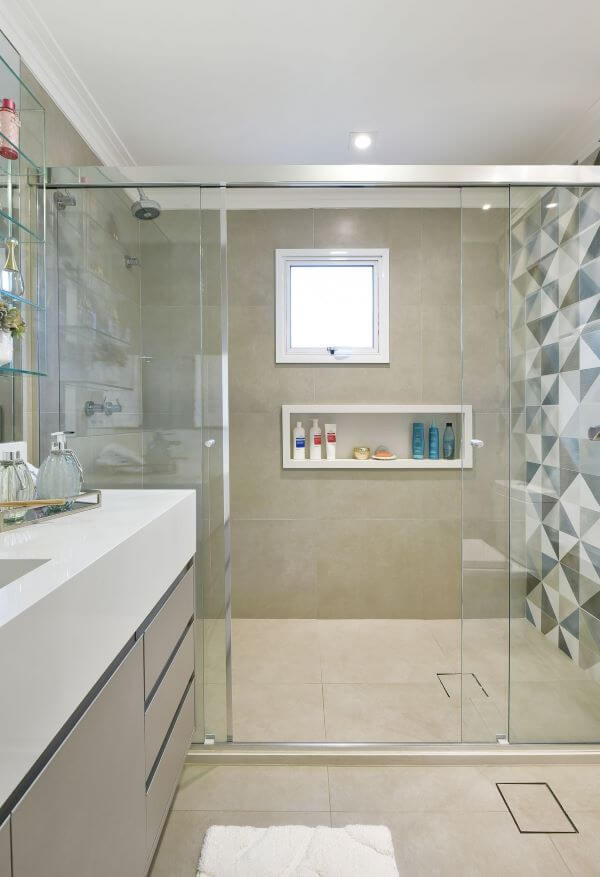 Banheiro revestido com piso porcelanato e bancada de quartzo branco para pia esculpida
